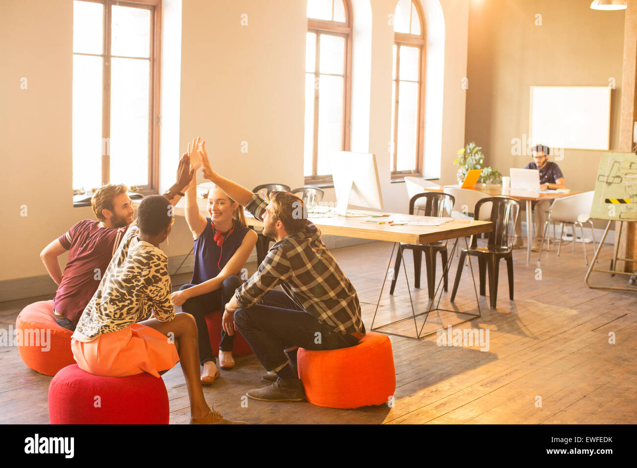 Casual business people joining hands in meeting in office - Stock Image