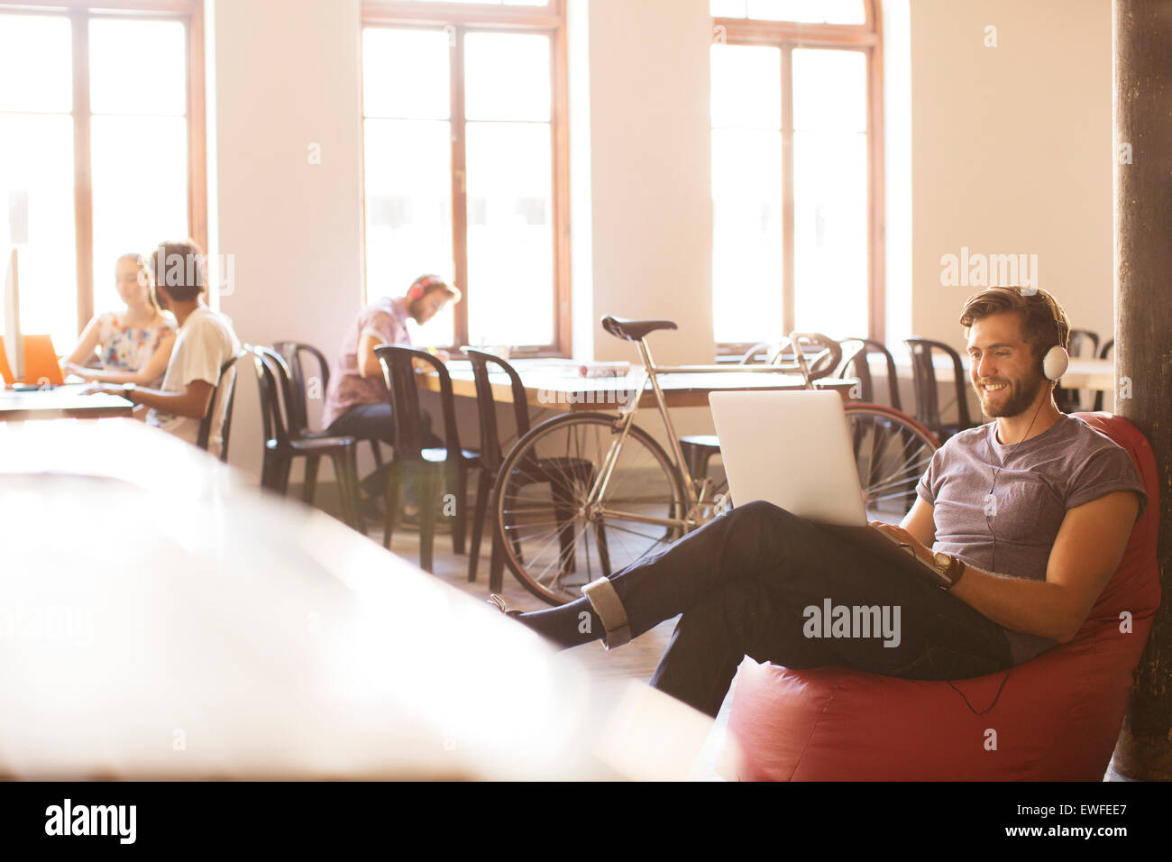 Smiling casual businessman wearing headphones and working at laptop on bean bag chair in office - Stock Image