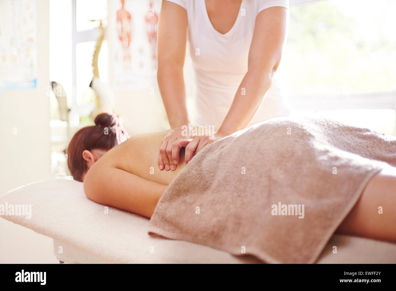 Woman receiving massage by masseuse - Stock Image