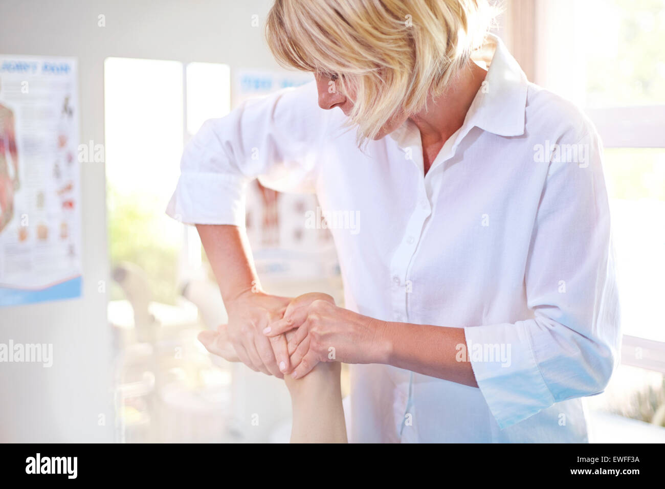 Physical therapist massaging patient's foot Stock Photo