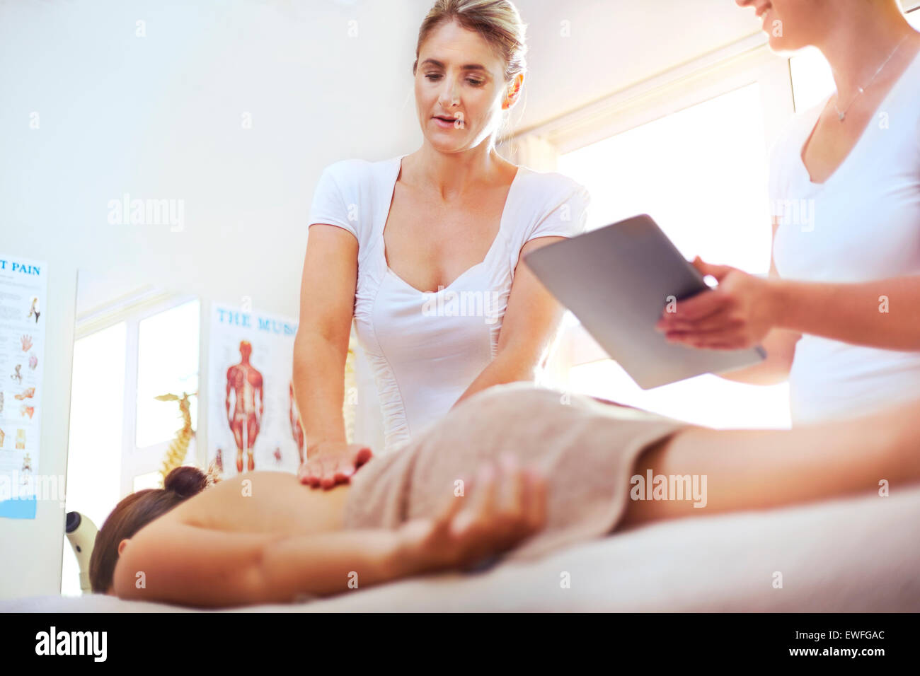 Physical therapists with digital tablet massaging woman's back Stock Photo