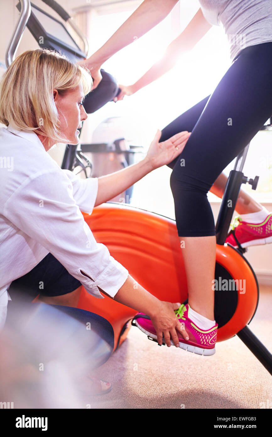 Physical therapist guiding woman's leg on stationary bike - Stock Image