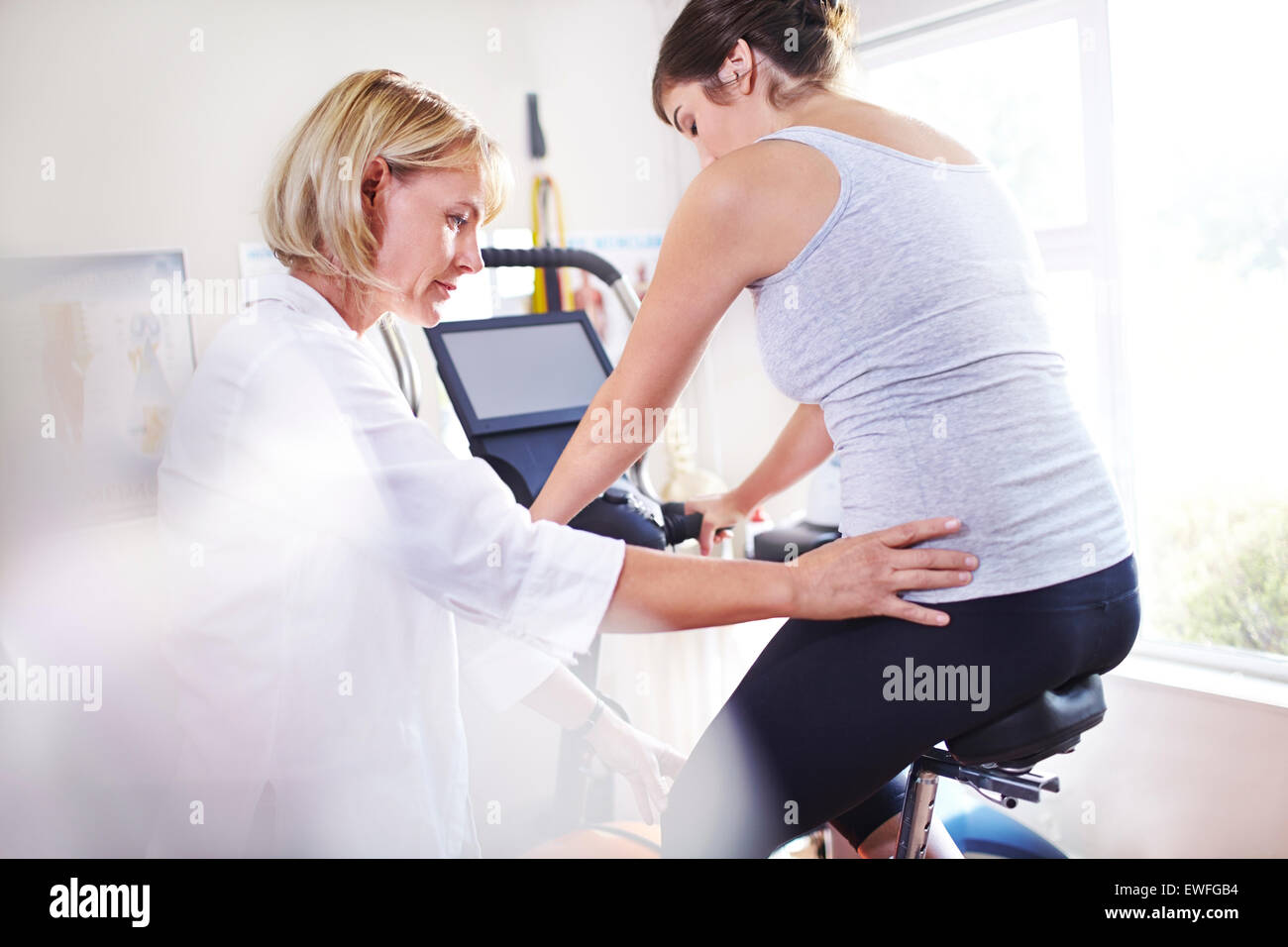 Physical therapist guiding woman's hips on stationary bike - Stock Image