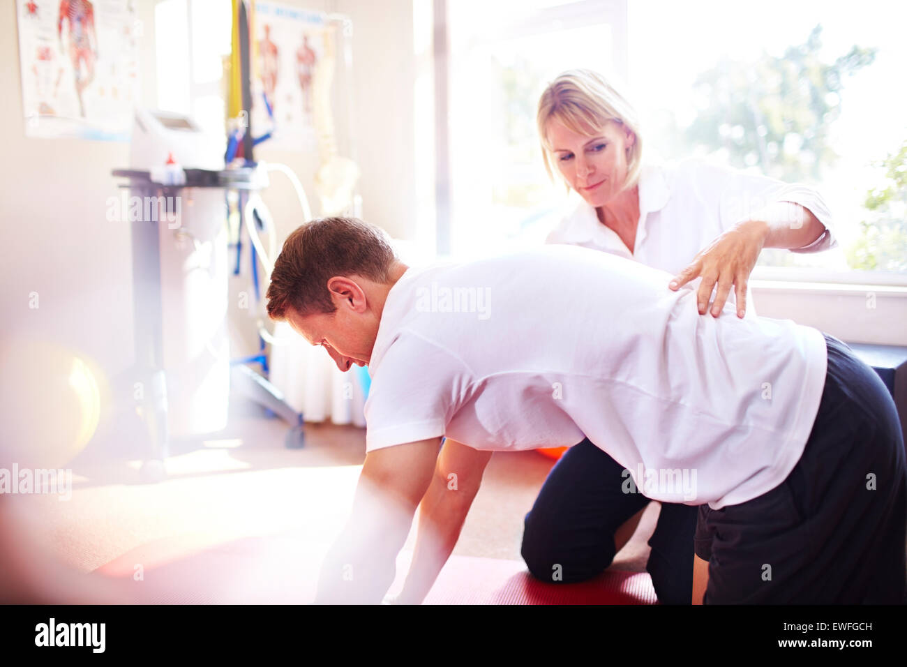 Physical therapist guiding man's back Stock Photo