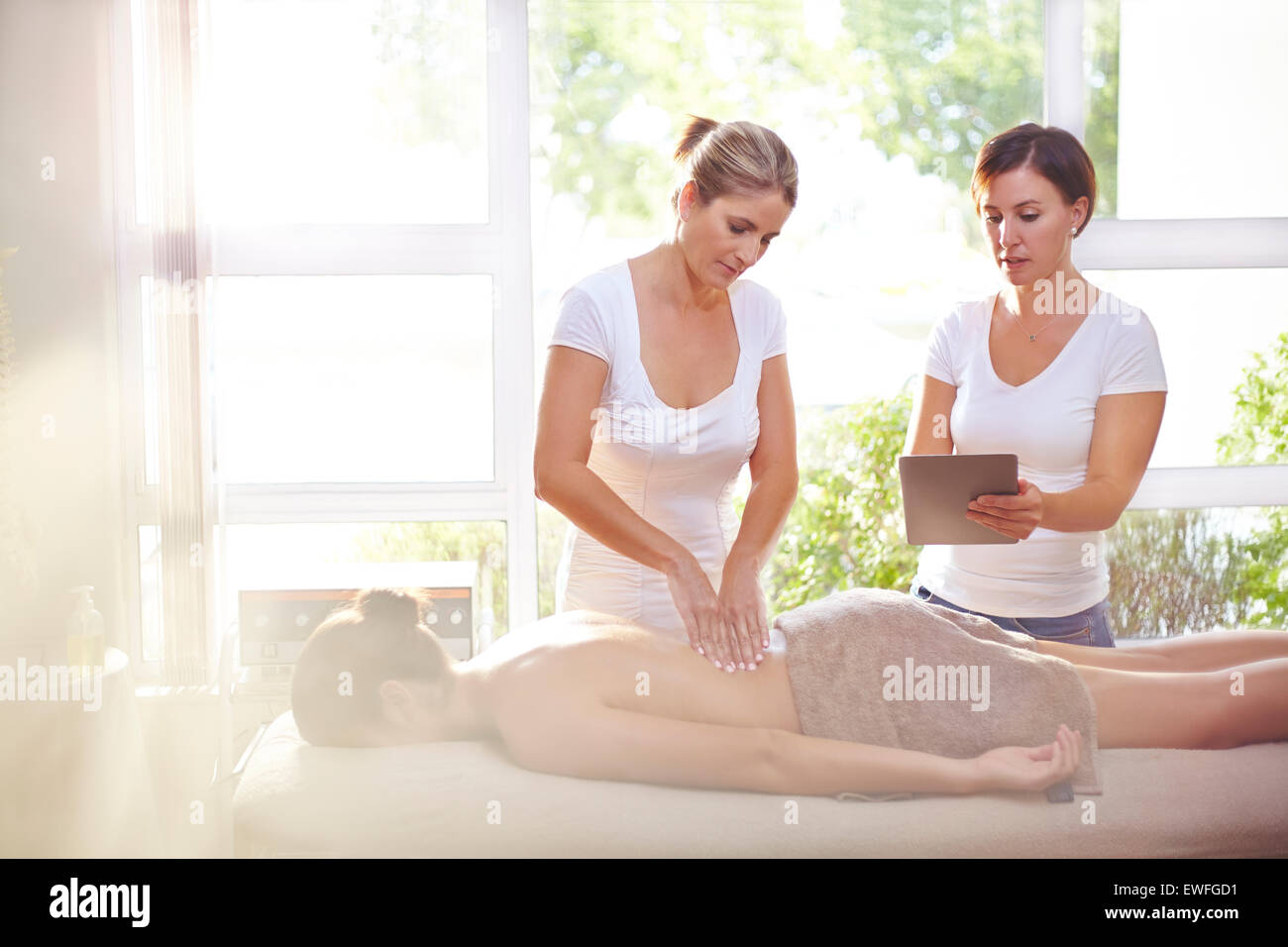 Masseuses with digital tablet massaging woman's back - Stock Image