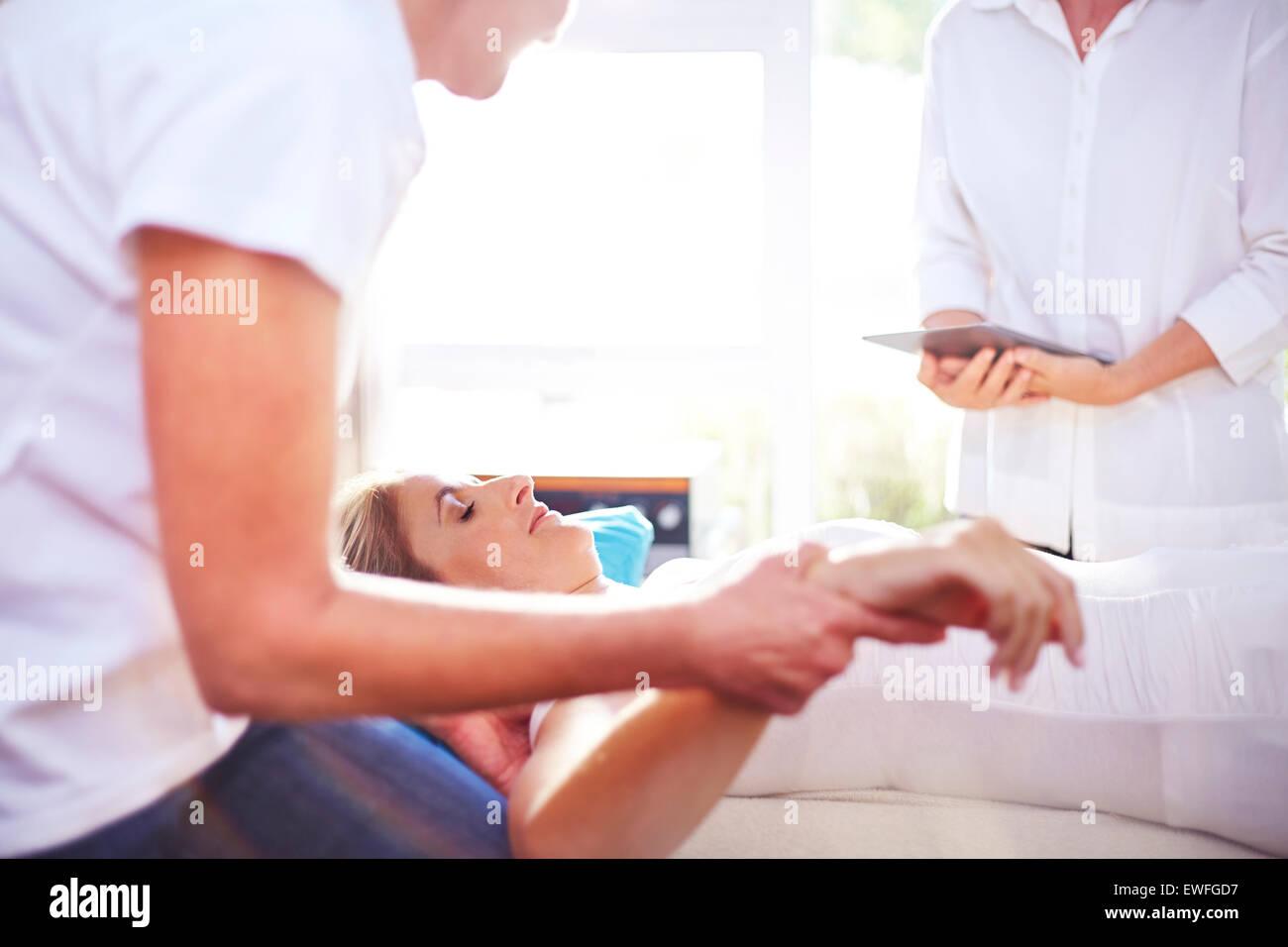 Masseuse massaging woman's hand - Stock Image