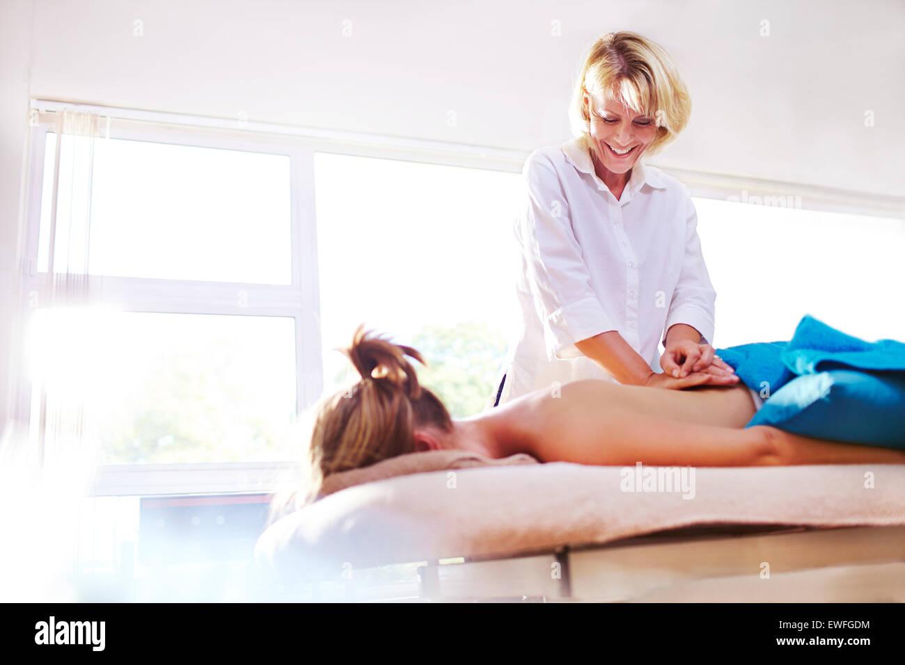 Masseuse massaging woman's back - Stock Image