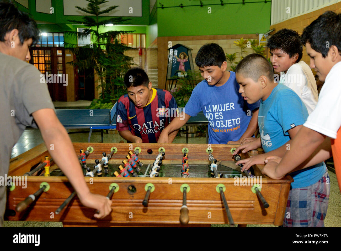 Teenagers playing foosball table, Lima, Peru - Stock Image