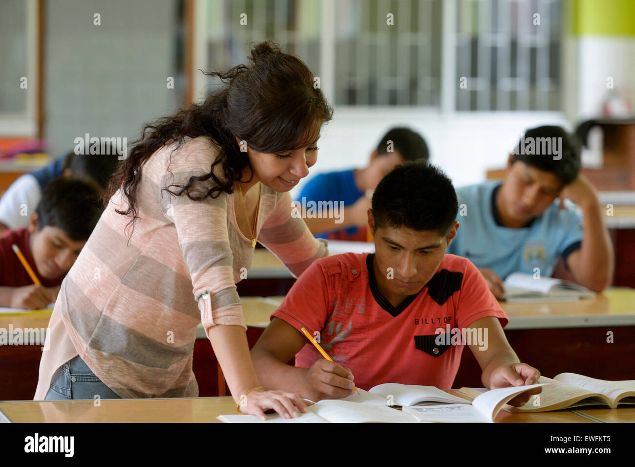 Social worker supporting a teenager, 15 years, former street child, doing homework, Brena, Lima, Peru - Stock Image