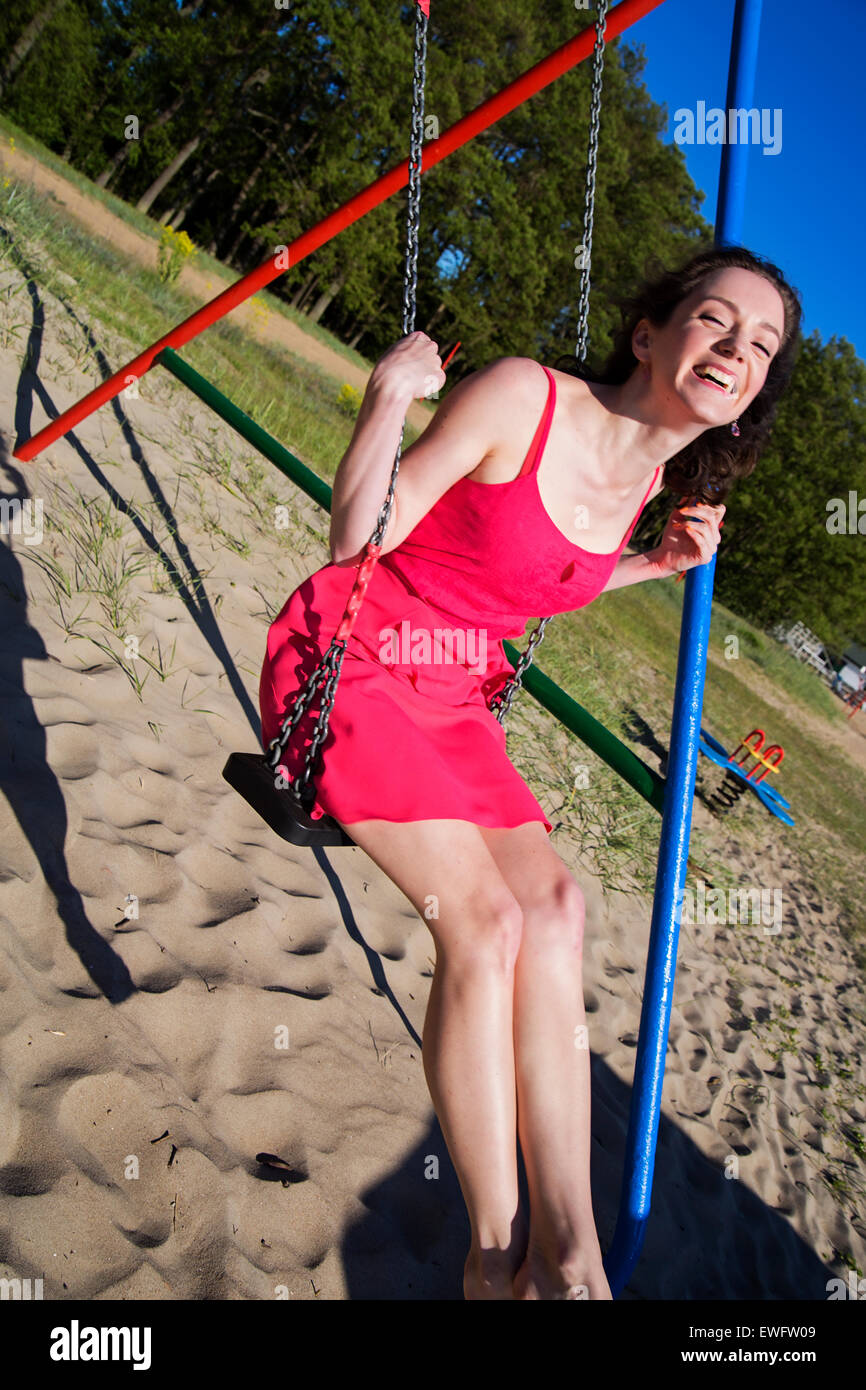 The young woman swinging at the beach - Stock Image