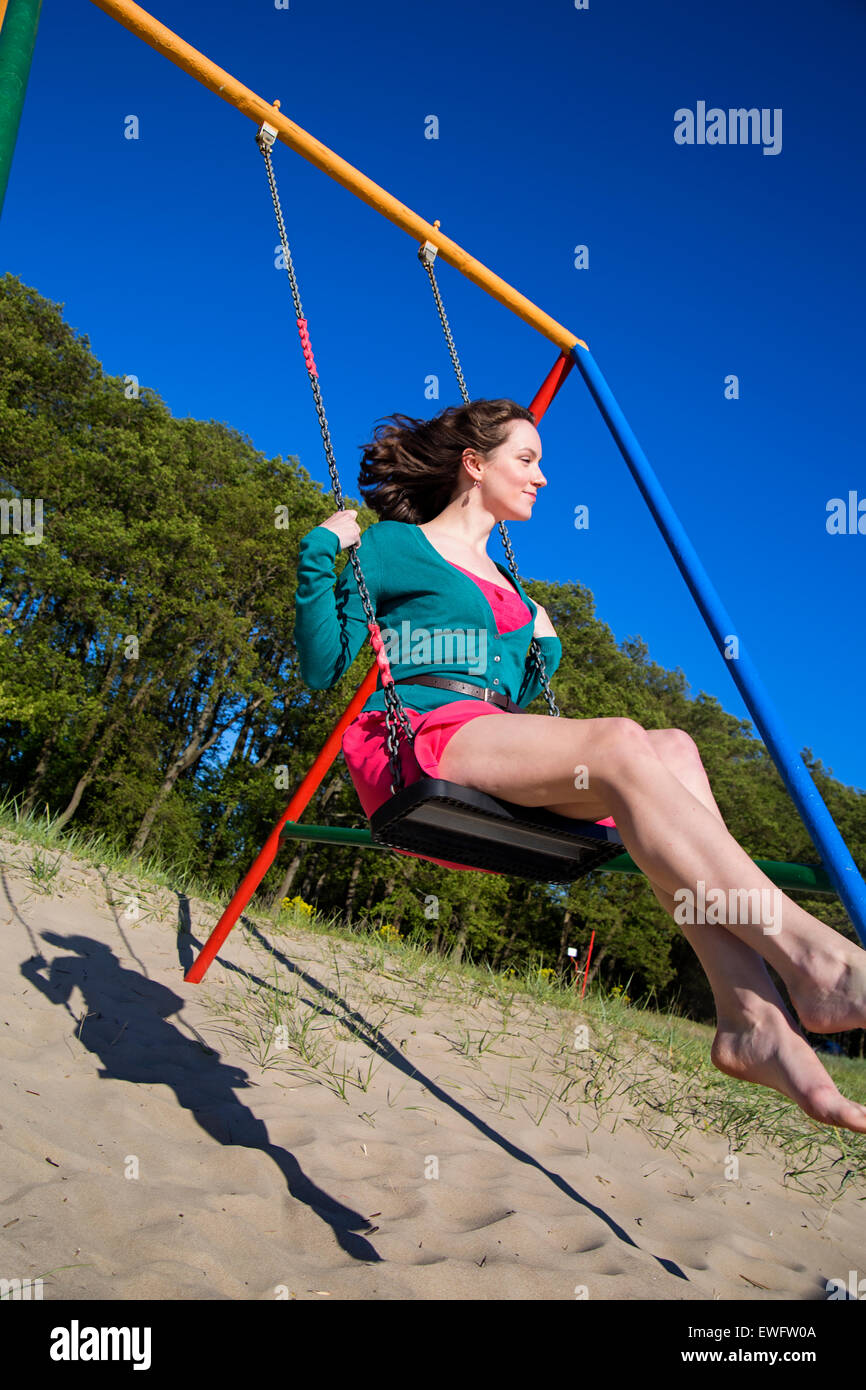 Romantic brunette swinging fast at the beach - Stock Image