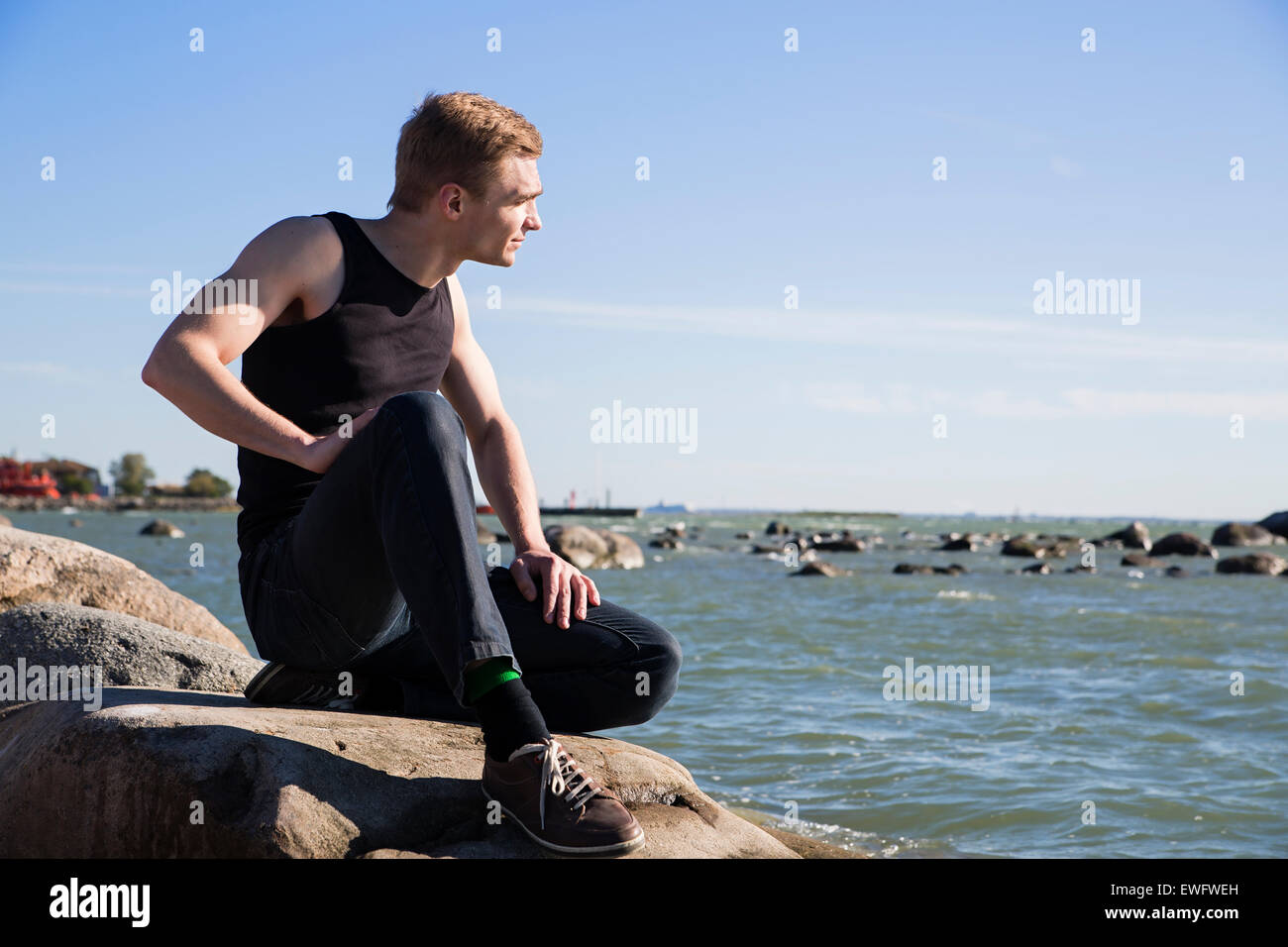 Focused serious man at the evening seaside - Stock Image