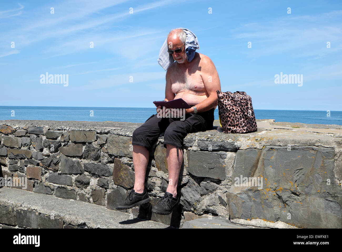 A senior man reads a kindle book with a tshirt protecting neck in hot sunshine at New Quay, Ceredigion Wales UK - Stock Image