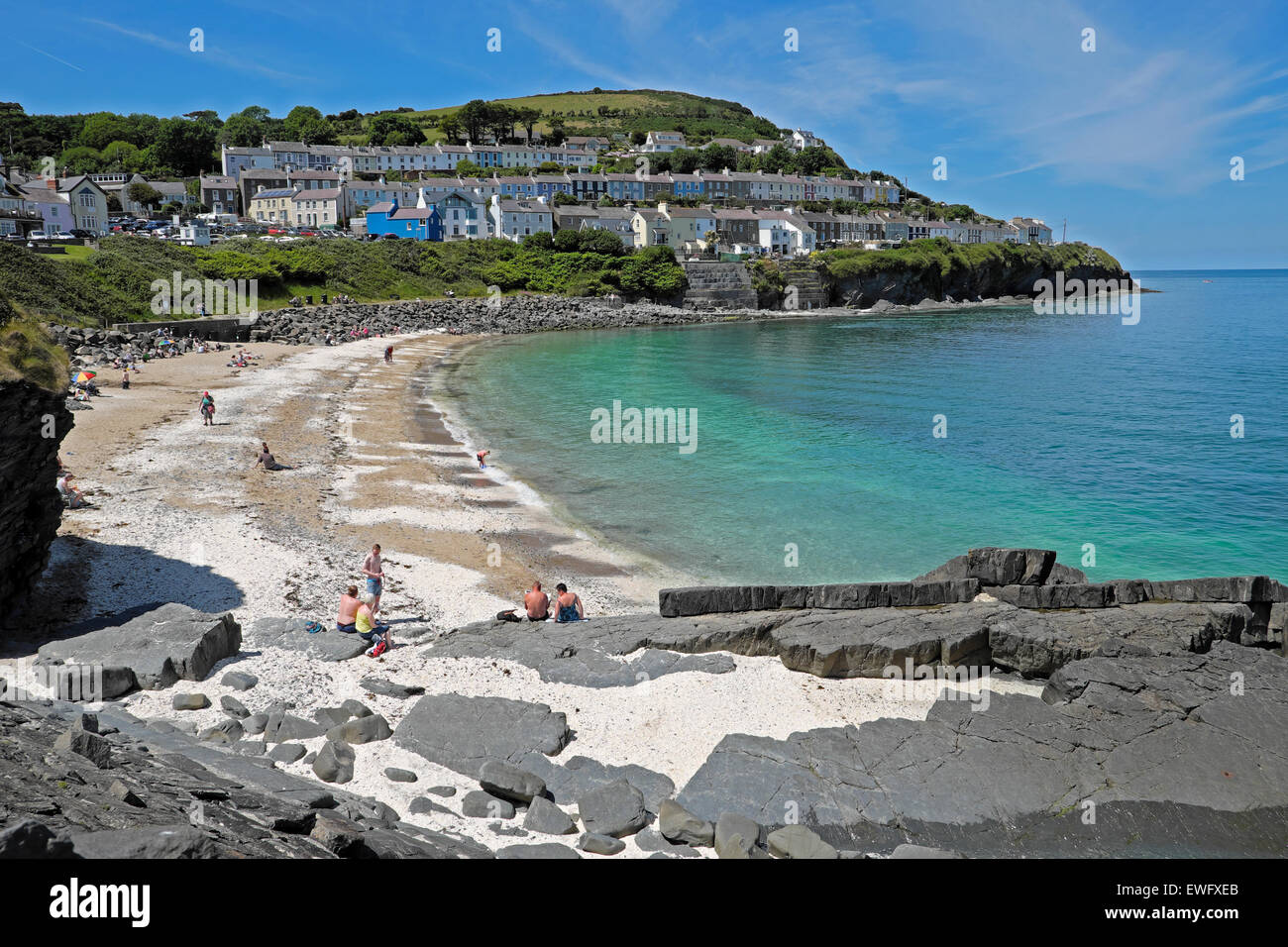 Beach on hot summer day in June with a view of terraced housing on hill New Quay, Ceredigion Wales UK  KATHY DEWITT - Stock Image