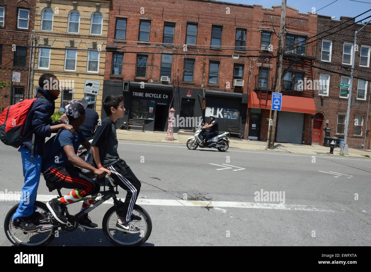 youths on bike cop on scooter brooklyn usa - Stock Image