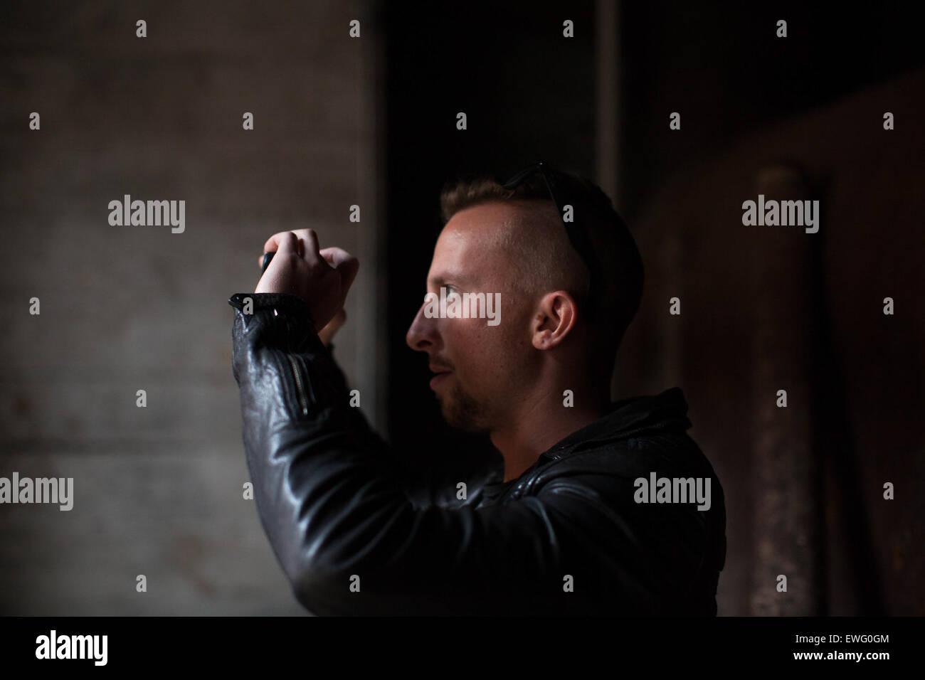 Man in Black Jacket Holding Camera - Stock Image