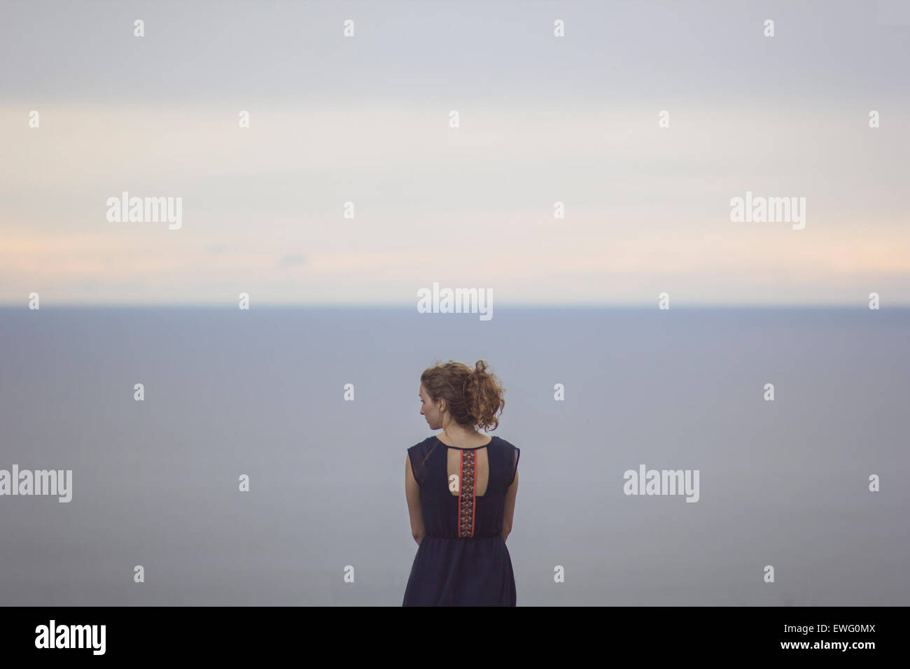 Female in Dress Seen from Behind with Head Turned - Stock Image