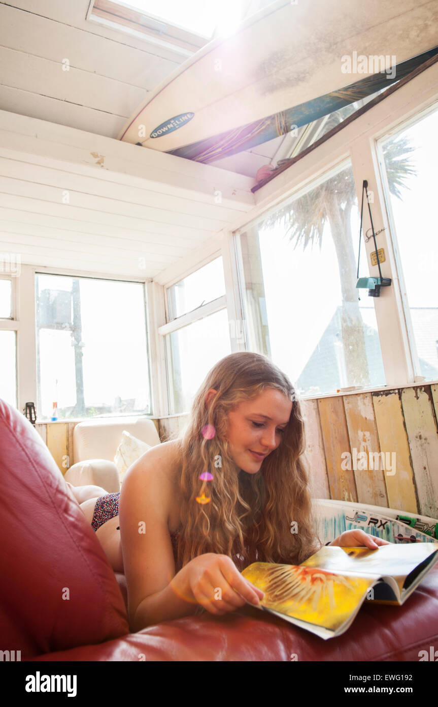 Surfer girl in a bikini hanging out at a beachhouse, on a hot summers day in Cornwall, UK. - Stock Image
