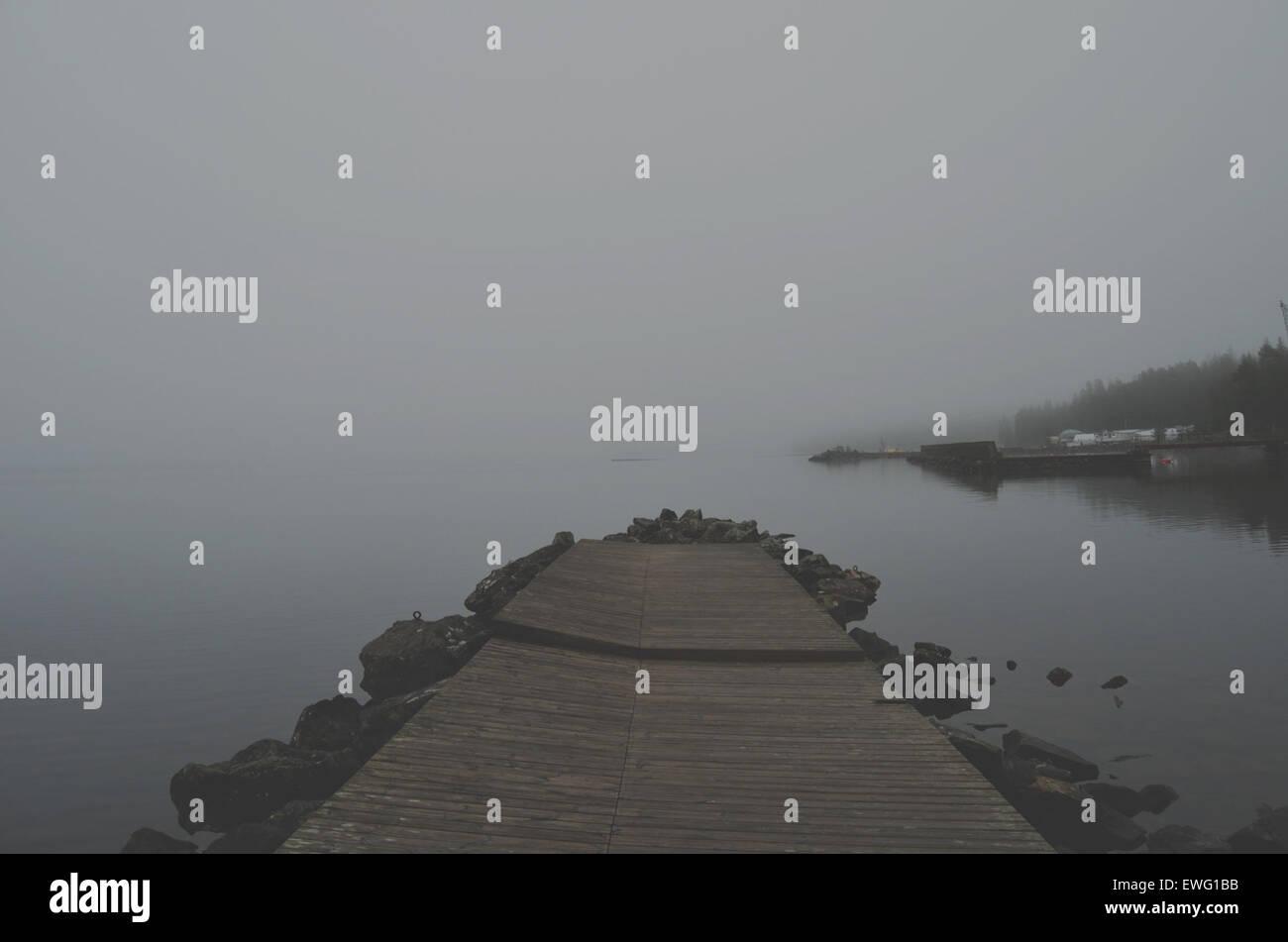 Misty Plank on Lake Ambiguous Cloudy Lake Misty Mysterious Overcast Pier Plank Water haze mist - Stock Image