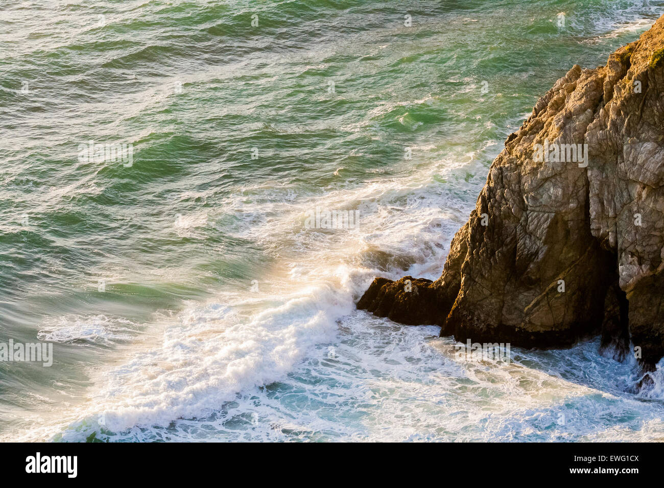 Ocean Waves Against Rocky Outcrop Outcrop Rock Tide Water White Water background ocean outdoor sea waves - Stock Image