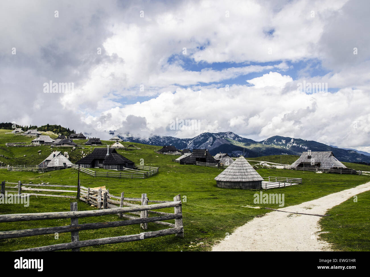 Path by Huts in Mountainous Region Clouds Cumulus fence homes houses huts landscape mountain outdoor path sky - Stock Image