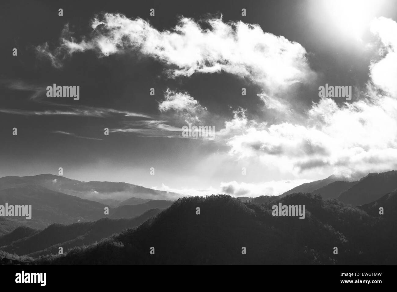 Black and White Landscape with Clouds Over Hills - Stock Image