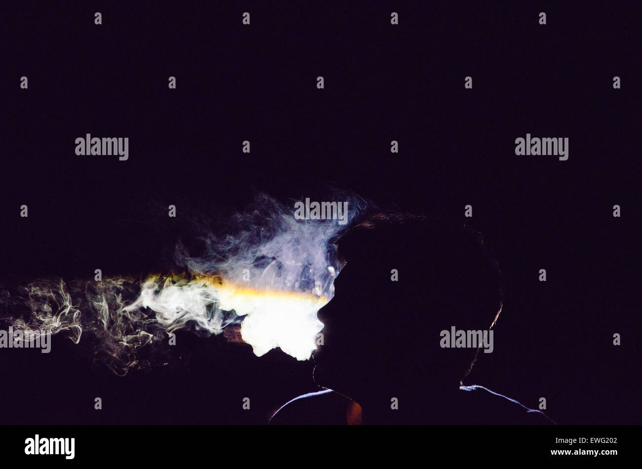 Silhouette of Person Blowing Smoke - Stock Image