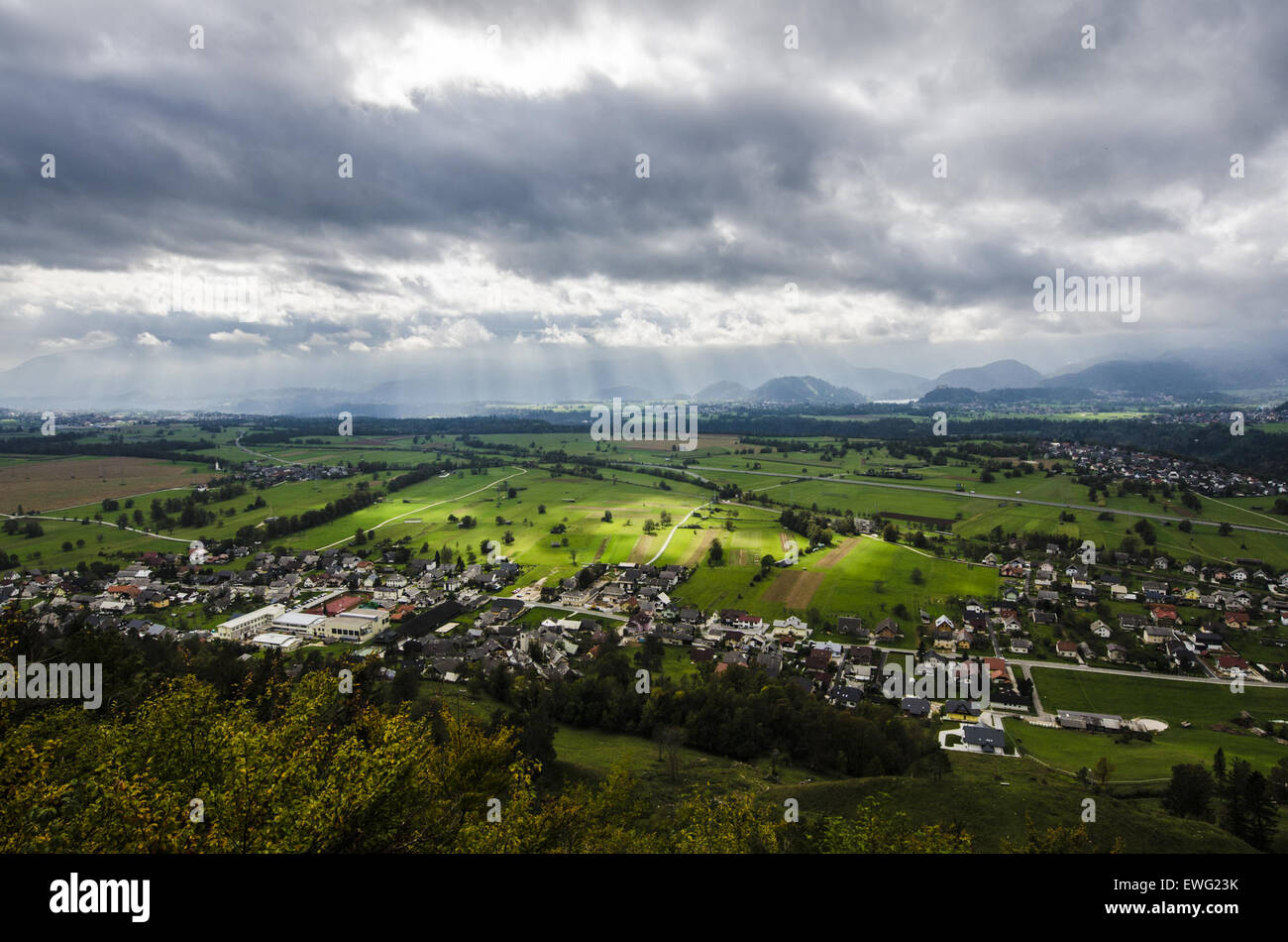 Wide-Angle View of Valley Community Clouds Wide-Angle grass green hills homes houses landscape outdoor suburbs - Stock Image