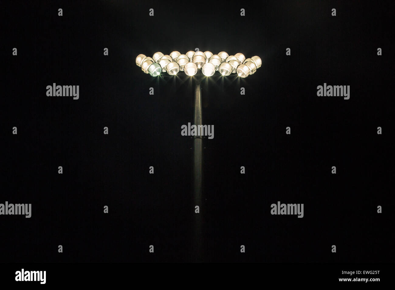 Bright Stadium Light on Black Background - Stock Image