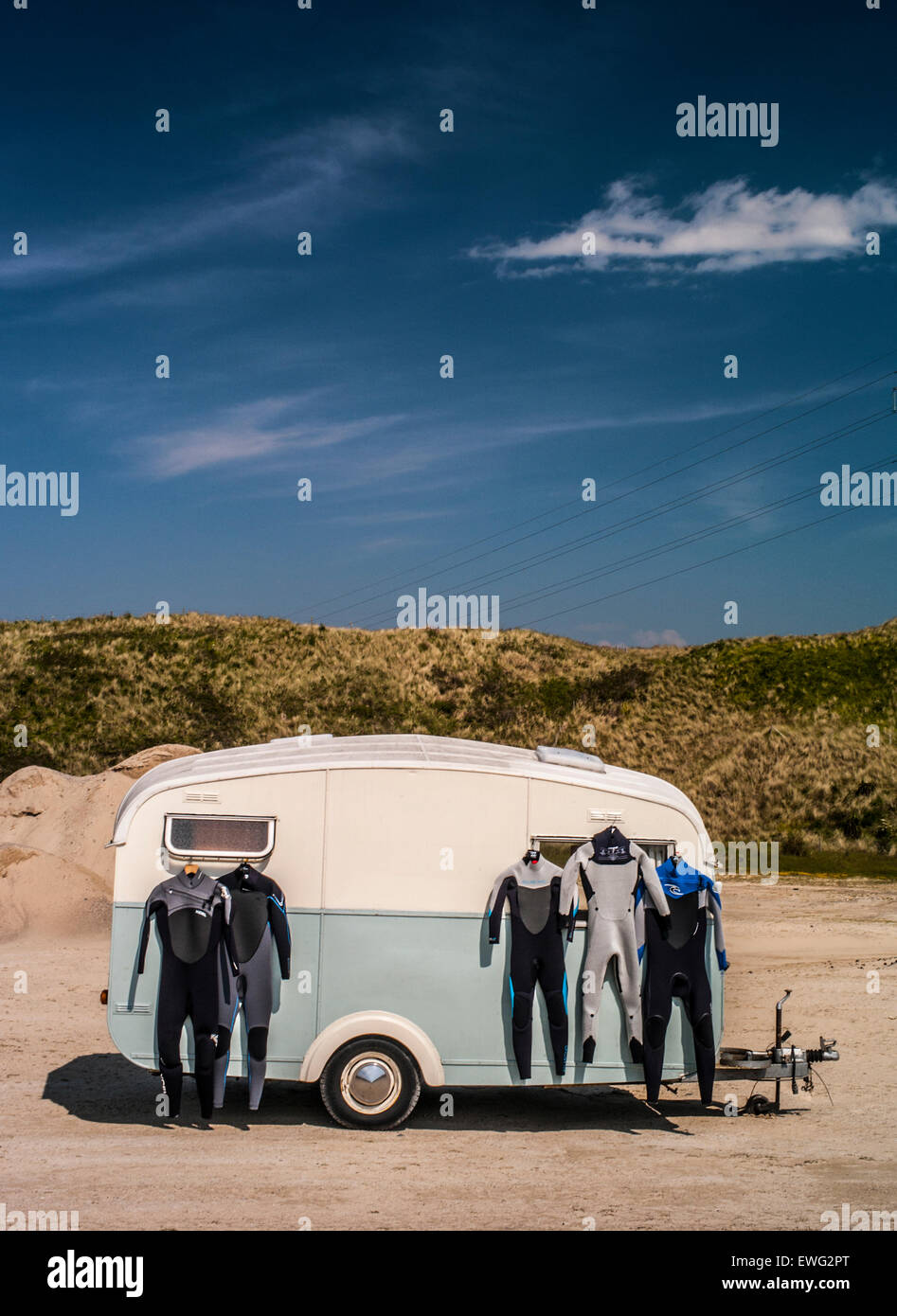 Wetsuits hanging on the side of a retro caravan with grasses and vivid blue sky in the distance. - Stock Image