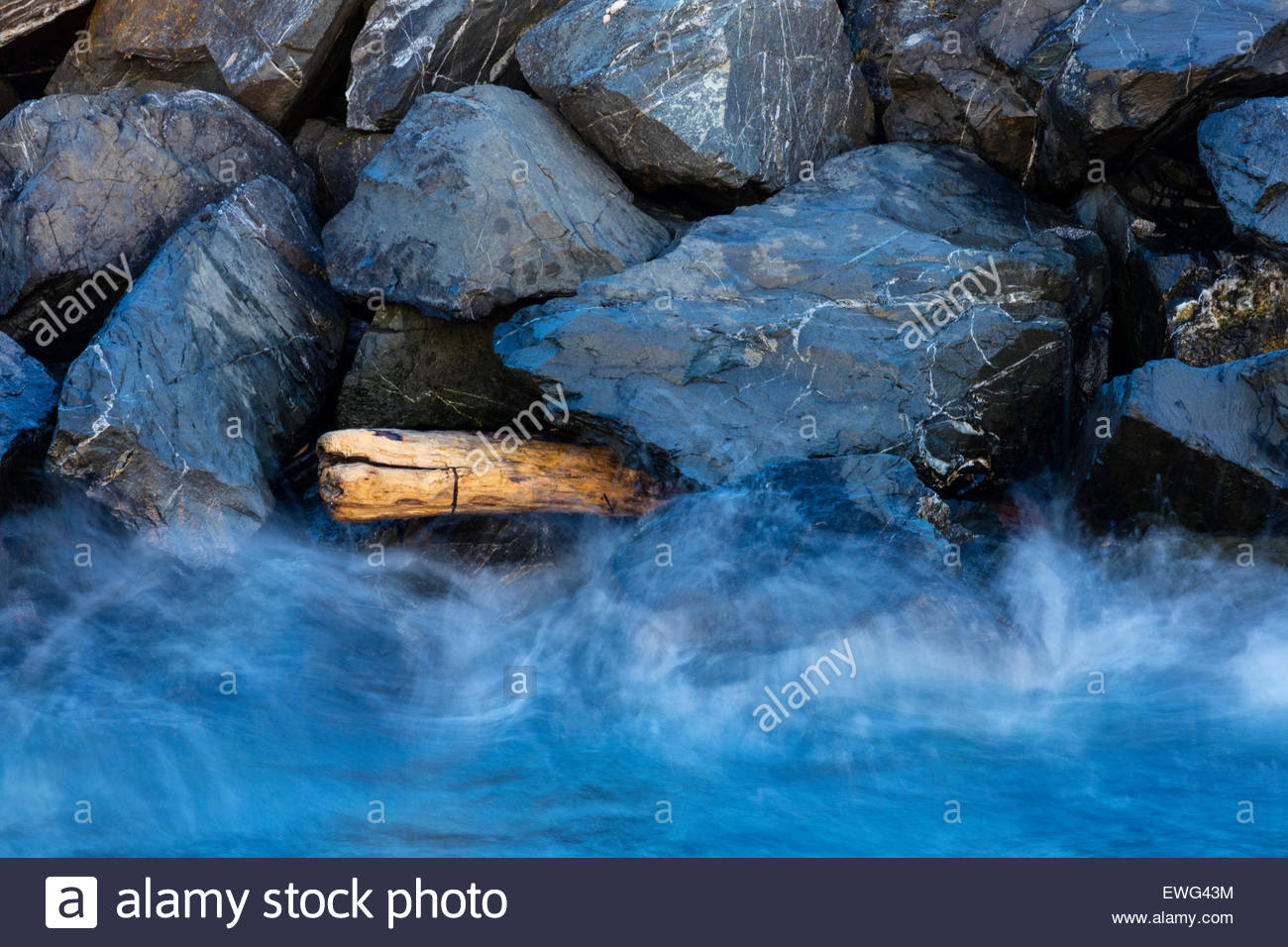 Waves from Puget Sound crash against driftwood stuck in a breakwater in Edmonds, Washington. - Stock Image