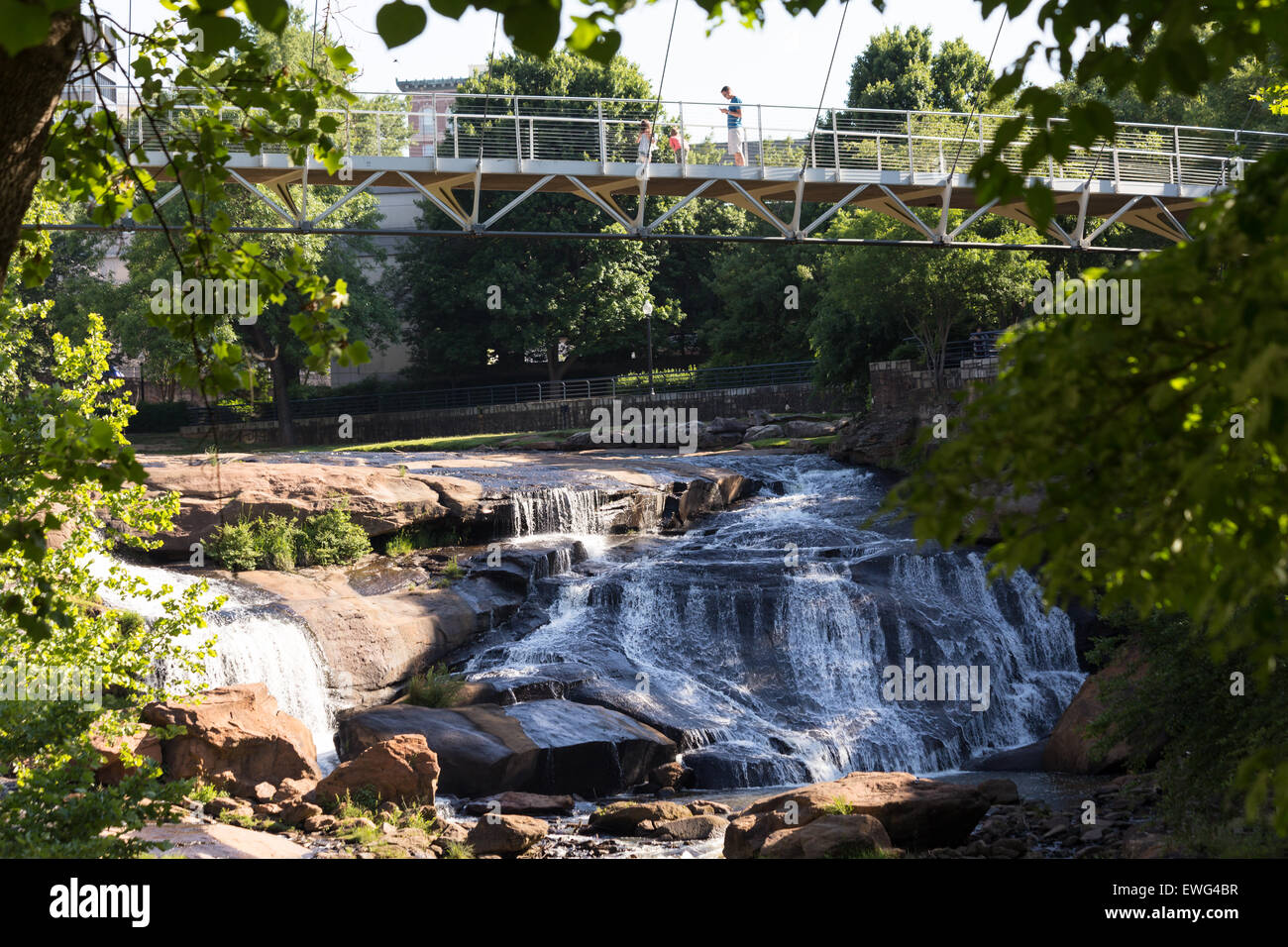 The Liberty bridge, a curved suspension bridge, crosses the Reedy River falls in beautiful and exciting downtown - Stock Image