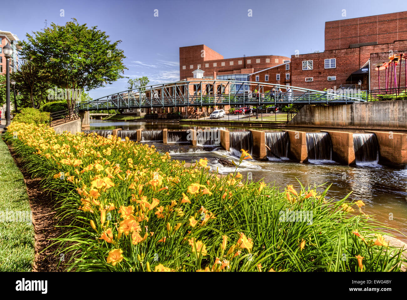 Tourists cross a bridge across the Reedy river in exciting and lively downtown Greenville, SC. - Stock Image