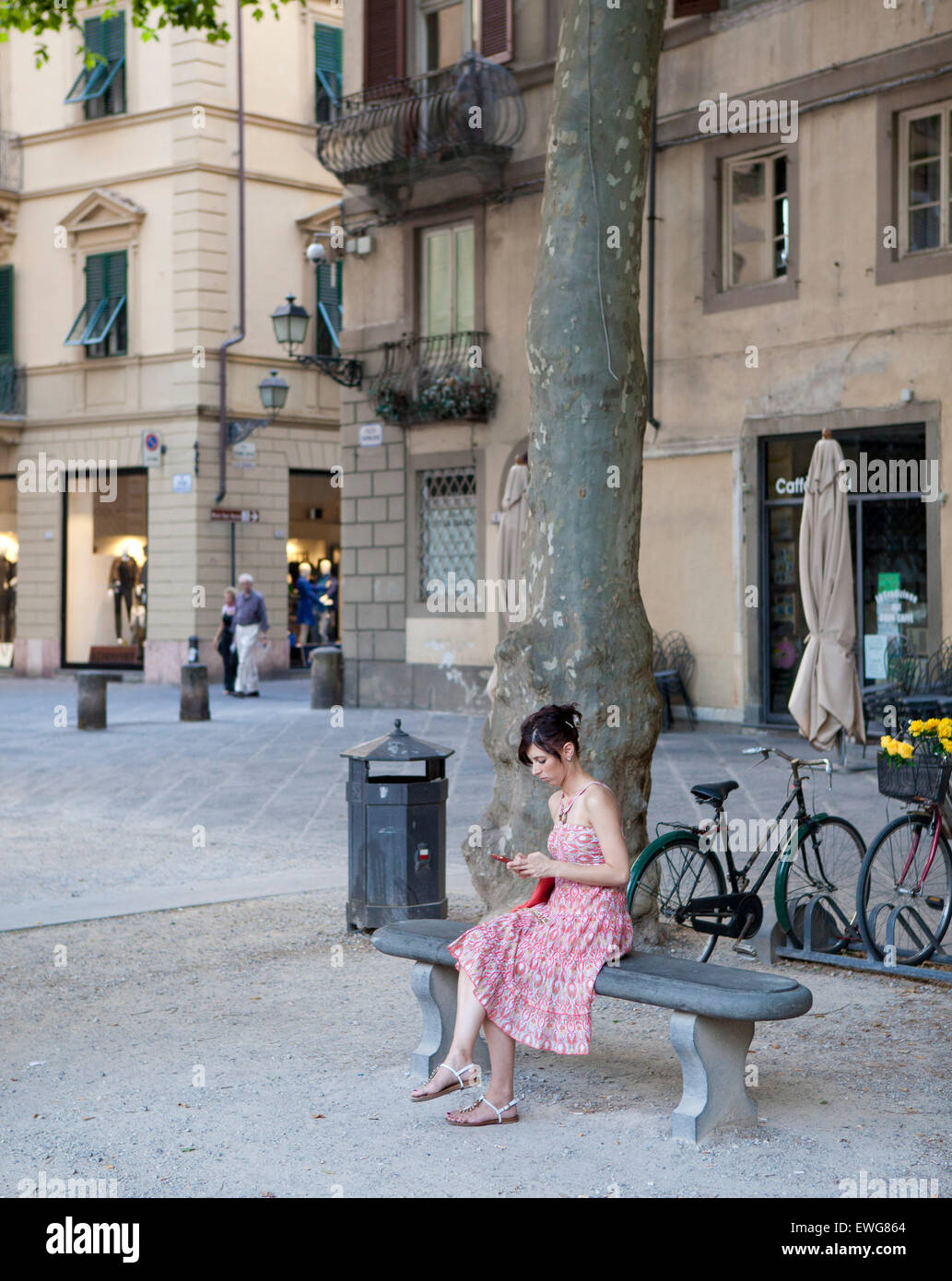 girl pink dress sitting on bench, Lucca Italy - Stock Image