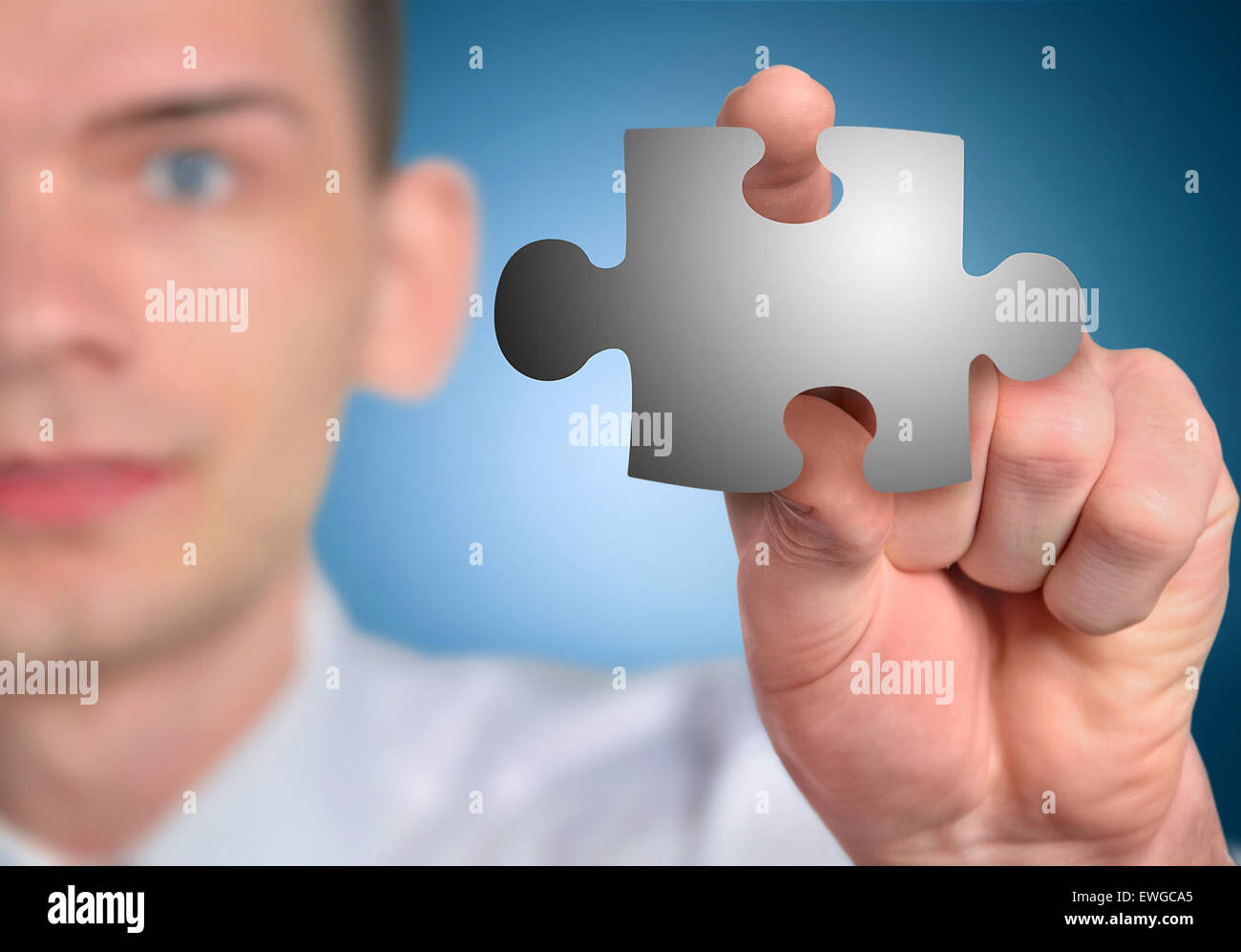 Man with puzzle piece in hand Stock Photo