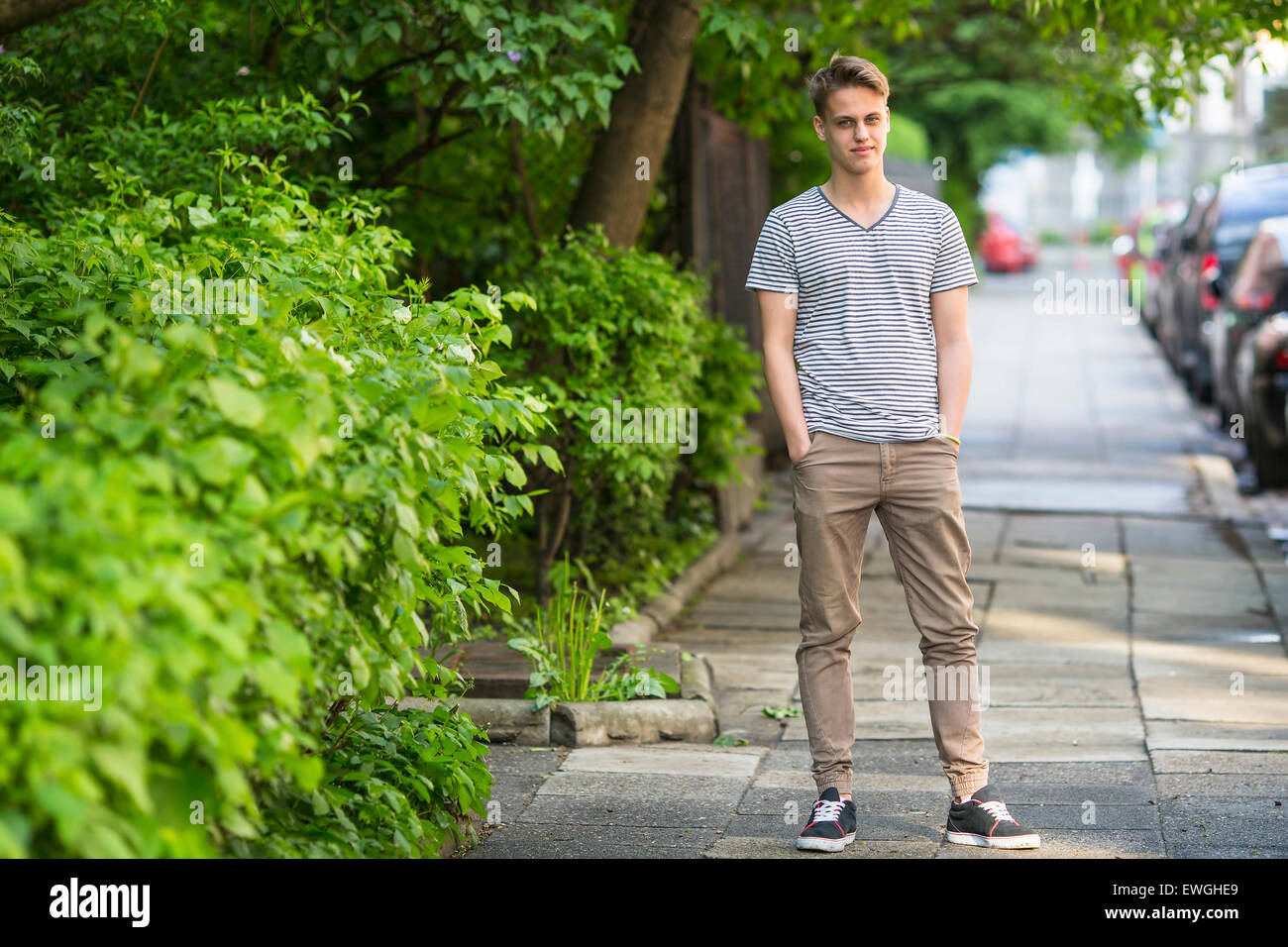 Young man standing on the summer street portrait in full growth. Stock Photo