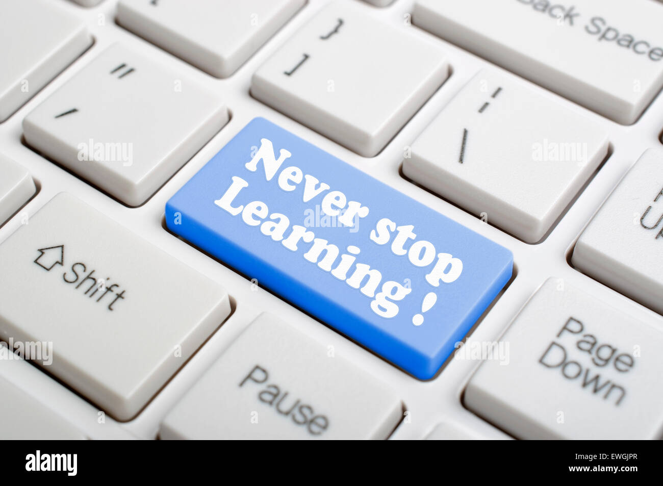 Blue never stop learning key on keyboard - Stock Image