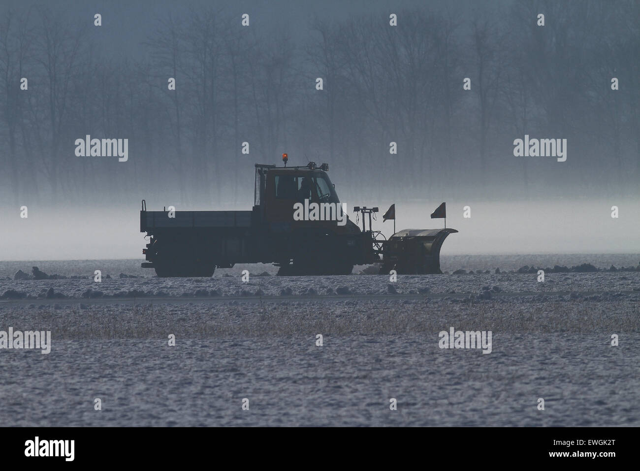 Snowplow removing snow at an airfield - Stock Image