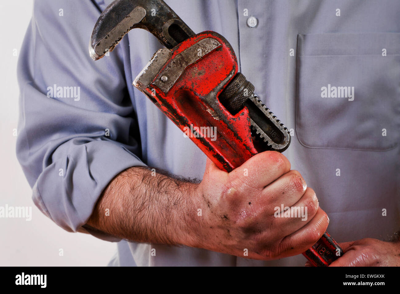 Stock image of plumber in uniform holding pipe wrench. - Stock Image