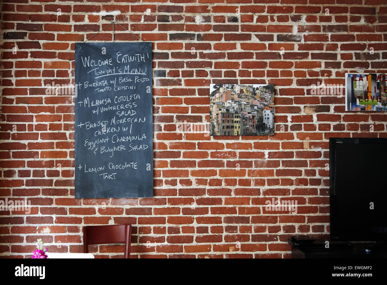 Red brick wall with chalk board menu - Stock Image