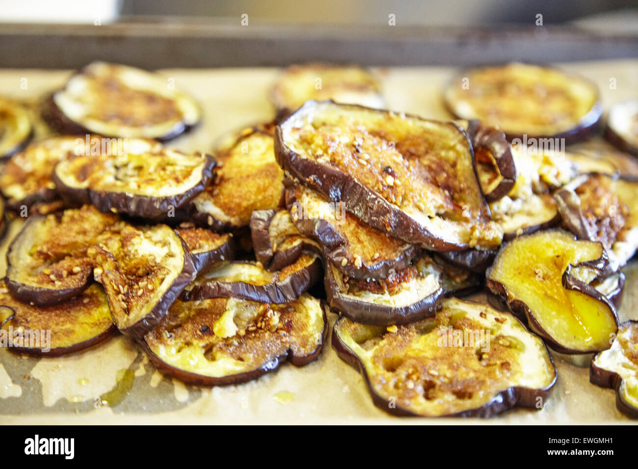 grilled eggplants on a cookie sheet on a grease paper bread crumbs on top - Stock Image