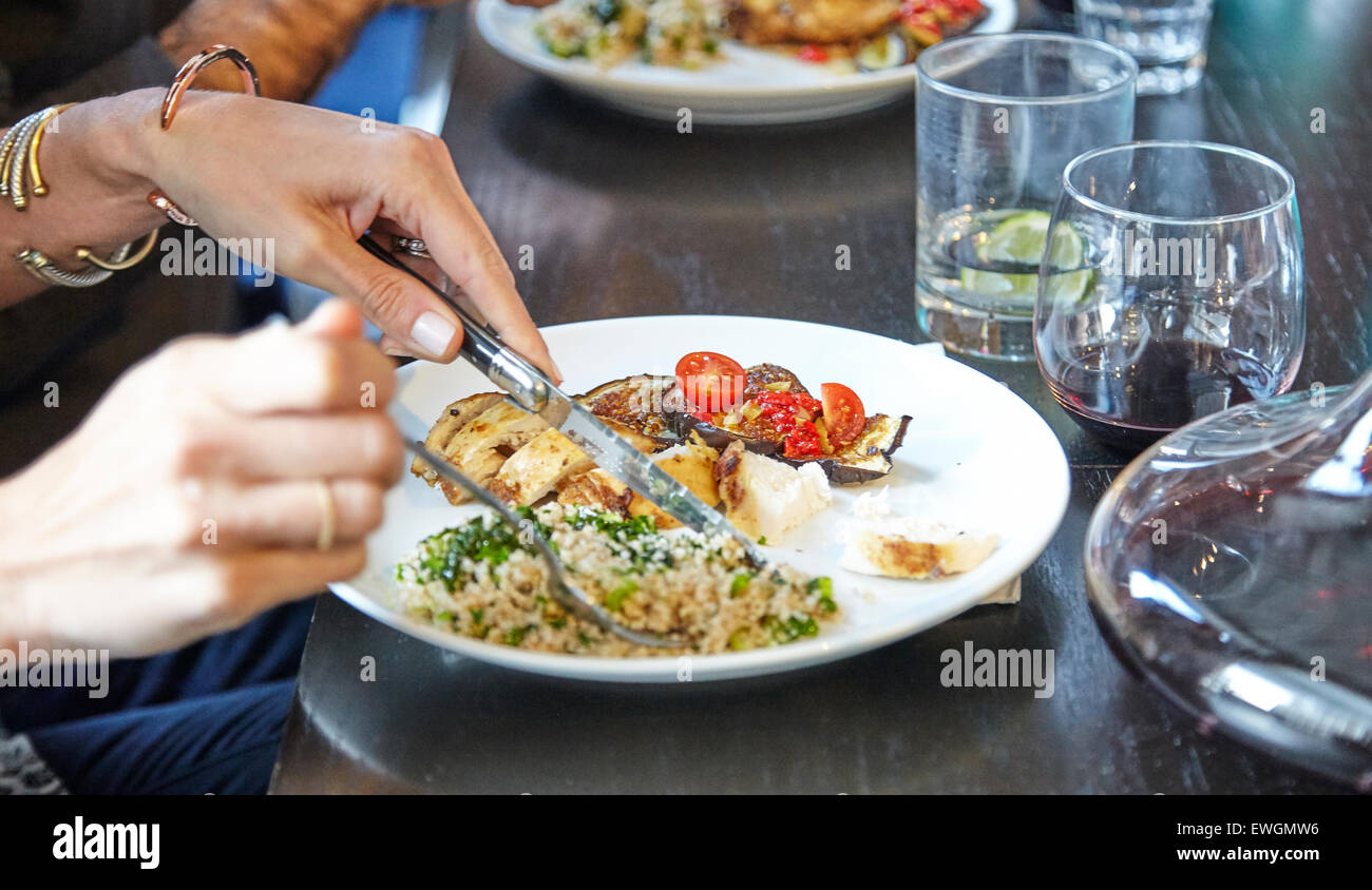 Grilled eggplant with couscous person eating it - Stock Image