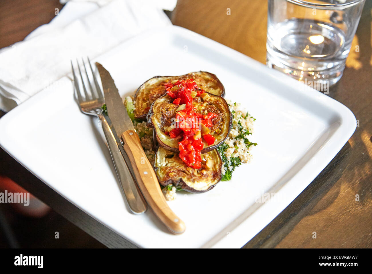 roasted eggplant with couscous on a white plate for and knife glass of water white napkin tomatoes on top roasted - Stock Image