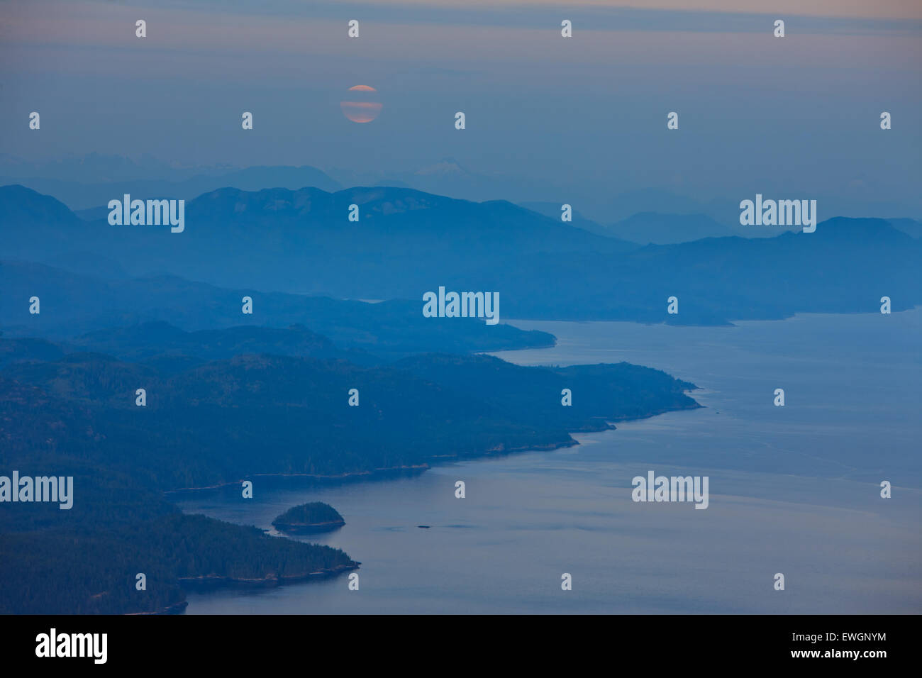 Looking over Johnstone Strait towards the British Columbia Coastal Mountains with a rising full moon at dusk, twilight, - Stock Image