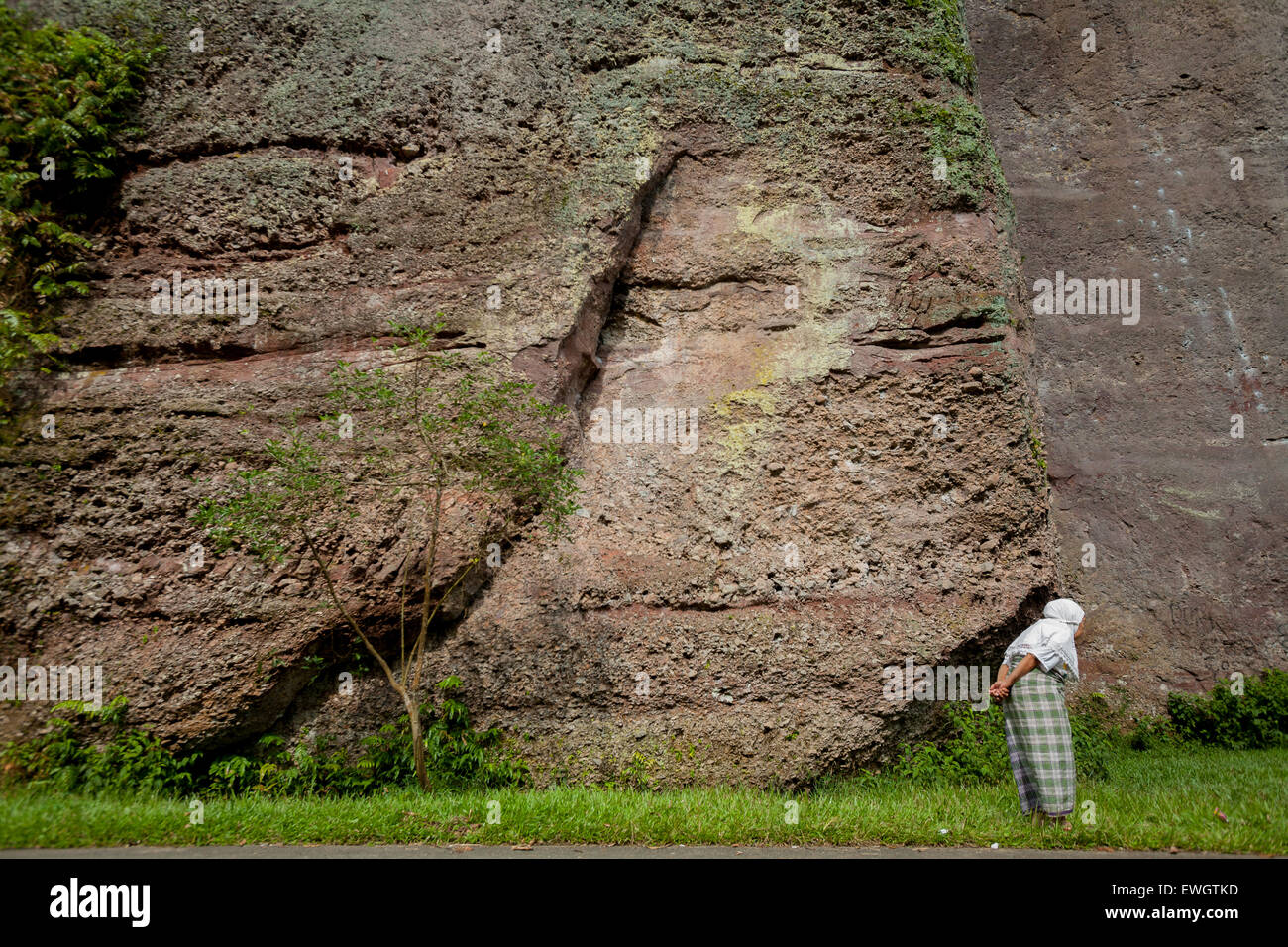 Old woman stands in front of cliff face in Harau Canyon in West Sumatra, Indonesia. - Stock Image