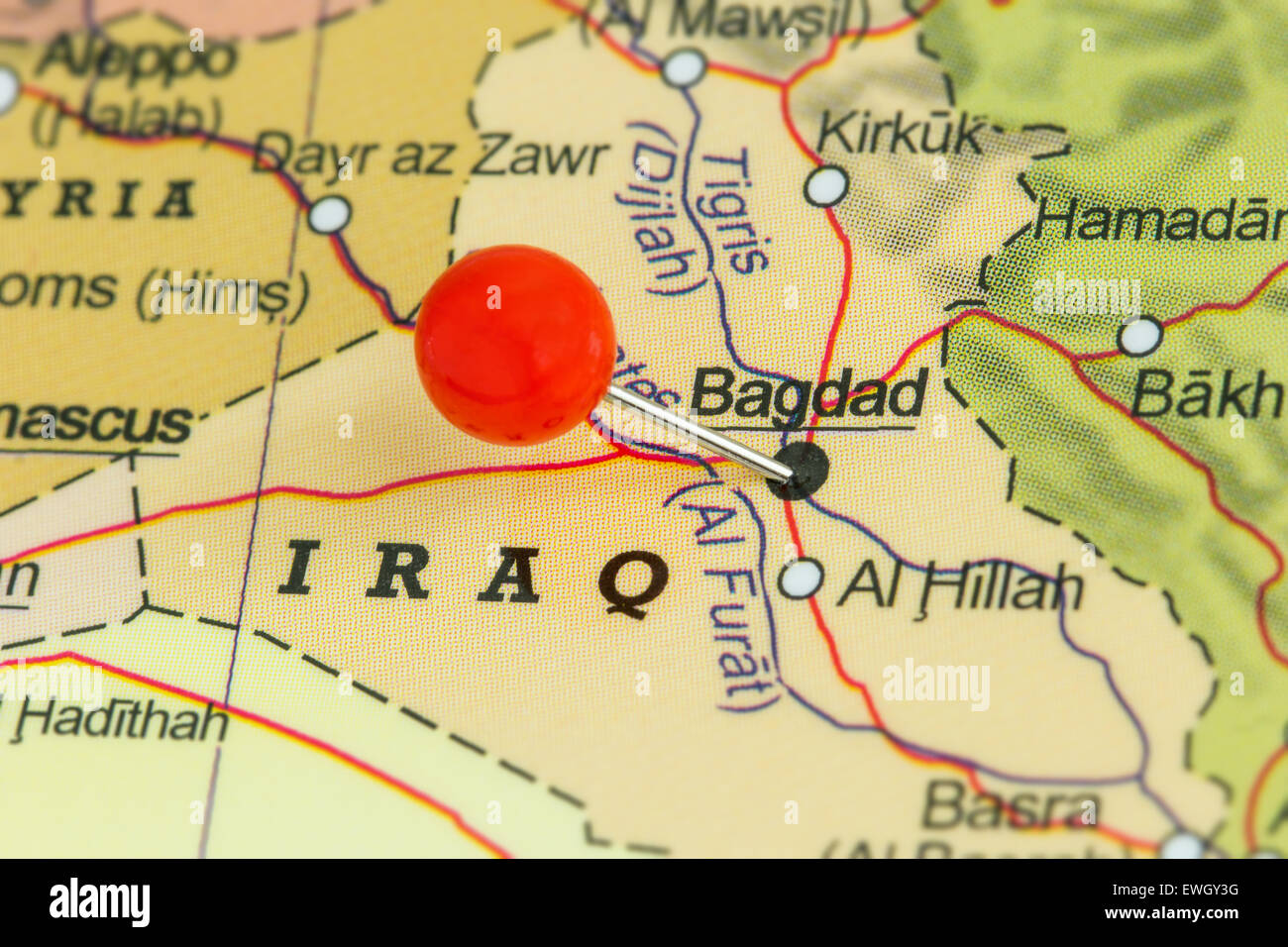 close up of a red pushpin on a map of baghdad iraq