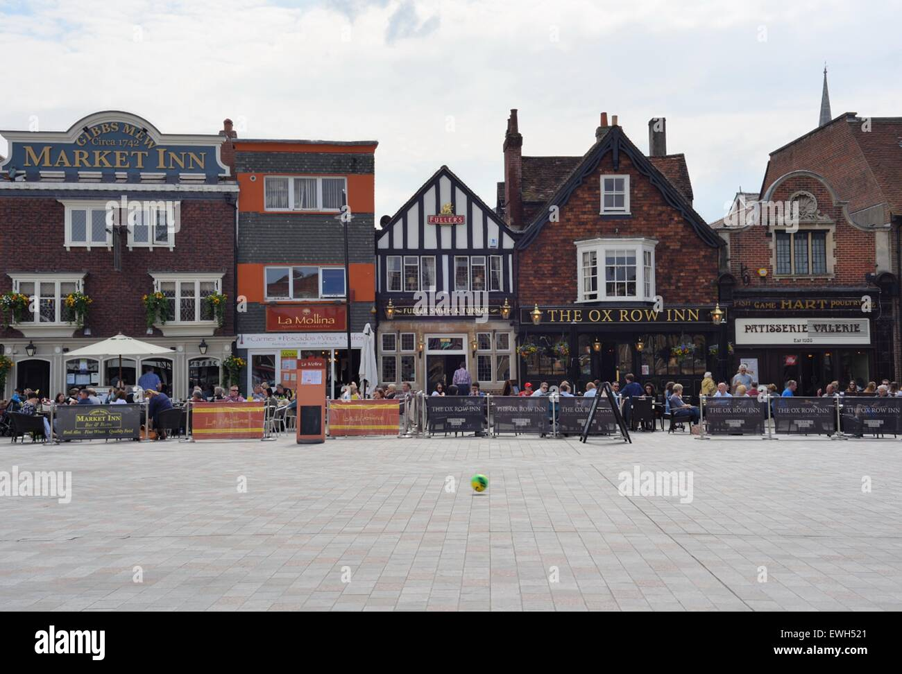 A football, kicked back and forth by two boys who are out of shot, bounces across the Market Square in Salisbury. - Stock Image
