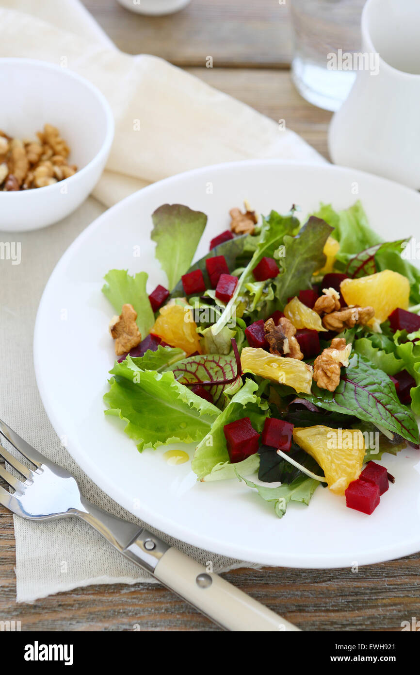 Delicious salad with nuts, vegetables and orange, healhty food - Stock Image