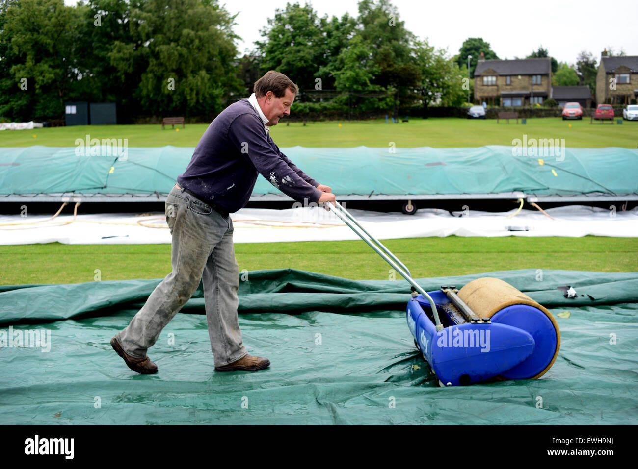 A groundsman soaking up rain water on the cricket pitch using a Bow Dry. Picture: Scott Bairstow/Alamy - Stock Image