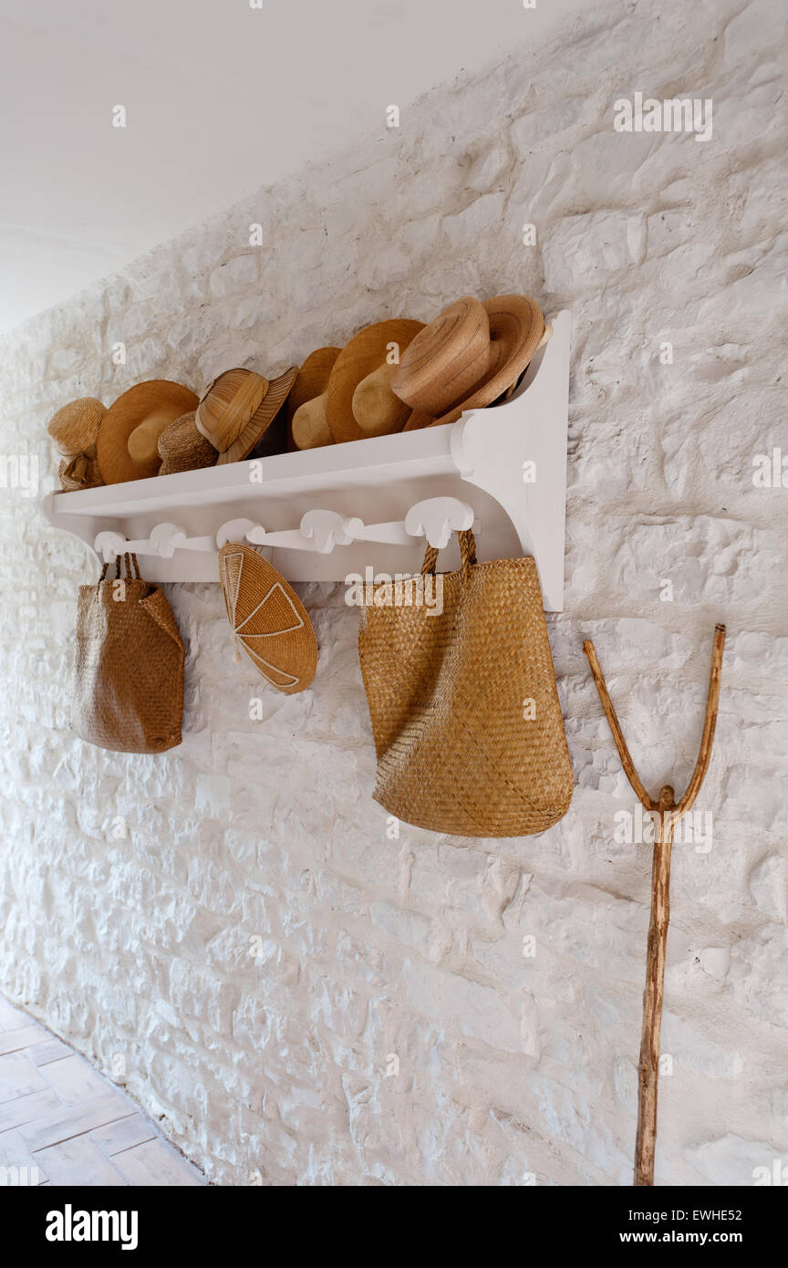 Straw sun hats on wooden rack against white stone wall - Stock Image